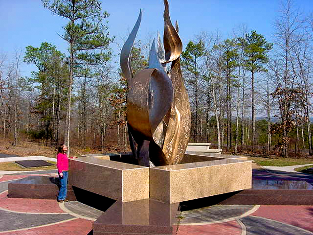 Eufaula artist Kathy Hamrick stands next to Sacred Fire, at the Chattahoochee Indian Heritage Center in Fort Mitchell, eastern Russell County.